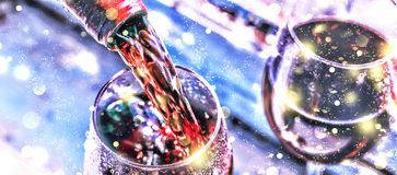 Pouring wine. Christmas wine. Christmas, falling snow, golden snowflakes. New Year. Close up stock image