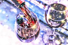 Pouring wine. Christmas wine. Christmas, falling snow, golden snowflakes. New Year. Close up stock photos