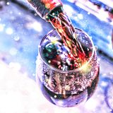 Pouring wine. Christmas wine. Christmas, falling snow, golden snowflakes. New Year. Close up royalty free stock images
