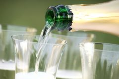 Pouring wine. Close-up of bottle and pouring sparkling wine royalty free stock photo