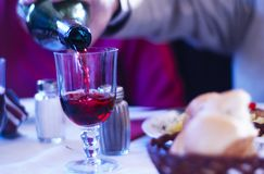 Pouring Wine With Dinner Blue Tint. Wine being poured to accompany family dinner at Pogor House in Iasi, Romania.  Blue tint added Royalty Free Stock Image