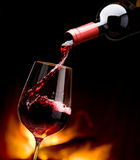 Pouring wine by the fireplace. Art pouring wine by the fireplace Stock Image