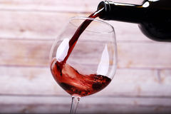 Pouring wine into glass and background stock photo