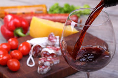 Pouring wine into glass and food background royalty free stock photos
