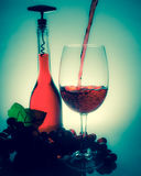 Pouring wine in a glass next to a bottle of wine and grapes on a Royalty Free Stock Photos