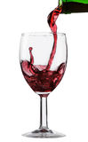 Pouring wine into a glass on a white background.  Stock Photo