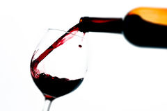Pouring wine glass on white background. Tilt shift selective focus effect Royalty Free Stock Photography