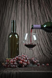Pouring wine with grapes Royalty Free Stock Photography