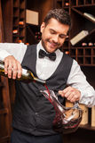 Pouring wine to decanter. Confident male sommelier pouring red wine to the decanter and smiling while standing near the wine shelf Stock Photography