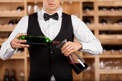 Pouring wine to decanter. Cropped image of confident young sommelier standing in front of wine shelf and pouring wine to the decanter Royalty Free Stock Photos
