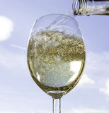 Pouring wine into a wine glass. Wine being poured with the sky in the background Royalty Free Stock Photo