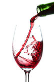 Pouring wineglass. With red wine on white background Royalty Free Stock Image