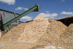Pouring wood-chips. Pouring wood chips in a lumber yard royalty free stock images
