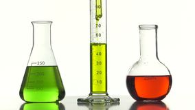 Pouring of a yellow liquid  into a graduated tube. Three bottles of different shapes and colors on a white background stock footage