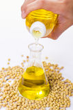 Pouring yellow soya bean oil. Into test tube glass stock images