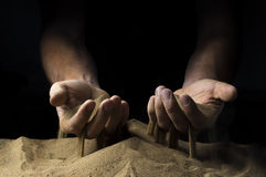 Pours sand from his hands. On a black background Stock Photos