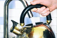 Pours water into a kettle from a tap stock photo