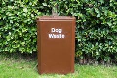 Poursuivez la poubelle brune de rebut sur l'herbe contre la haie en parc pour rester propre et rangé image libre de droits