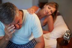 Épouse soulageant le mari souffrant avec l'insomnie Photographie stock libre de droits