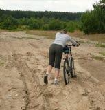 Poussée du vélo par les sables Photographie stock