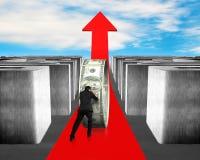 Poussant l'argent sur élever la flèche rouge par le labyrinthe Image libre de droits