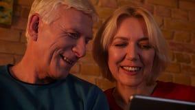 Pousse de plan rapproché des couples heureux âgés utilisant le comprimé se reposant sur le sofa à l'intérieur dans un appartement banque de vidéos