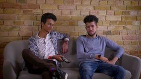 Pousse de plan rapproché de deux jeunes amis masculins regardant la TV ainsi que l'excitation se reposant sur le divan à l'intéri banque de vidéos