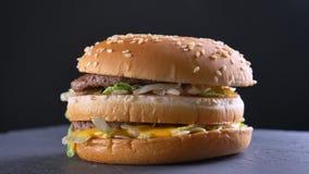 Pousse de plan rapproché de double cheeseburger appétissant avec deux petits pâtés juteux et les condiments banque de vidéos