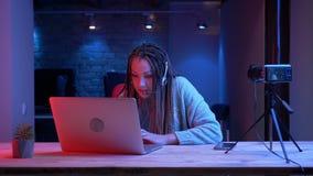 Pousse de plan rapproché du jeune blogger féminin attirant avec des dreadlocks dans des écouteurs dactylographiant sur l'ordinate banque de vidéos