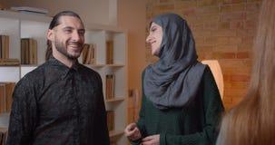 Pousse de plan rapproché du jeune coulpe musulman attrayant achetant un appartement serrant la main avec le realter et étreignant banque de vidéos