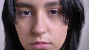 Pousse de plan rapproché du jeune joli visage femelle caucasien regardant directement la caméra avec le fond d'isolement banque de vidéos