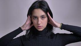 Pousse de plan rapproché du jeune modèle femelle caucasien magnifique posant devant la caméra avec le fond d'isolement banque de vidéos