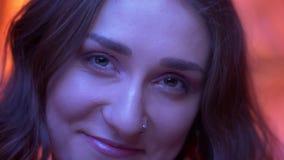 Pousse de plan rapproché du jeune visage femelle caucasien attrayant regardant la caméra avec l'expression du visage de sourire a banque de vidéos