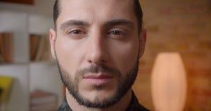 Pousse de plan rapproché du jeune visage masculin barbu musulman attrayant regardant la caméra à l'intérieur dans un appartement banque de vidéos