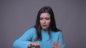 Pousse de plan rapproché de faire des gestes femelle de pantomime de jeune jolie brune et de papillon imaginaire avec le fond d'i clips vidéos