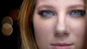 Pousse de plan rapproché de jeune beau visage femelle avec des yeux regardant le maquillage mignon de caméra avec le fond de bo clips vidéos