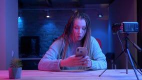Pousse de plan rapproché de jeune blogger féminin attirant avec la transmission de messages de dreadlocks sur couler de téléphone banque de vidéos