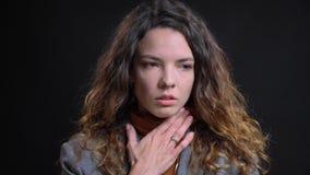 Pousse de plan rapproché de jeune femelle caucasienne attirante avec les cheveux bouclés de brune ayant une gorge malade et étant photo libre de droits