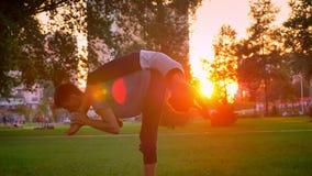 Pousse de plan rapproché de jeune femelle et de mâle attirants exécutant une pose d'acroyoga dans le parc avec le coucher du sole banque de vidéos