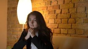 Pousse de plan rapproché de jeune jolie TV de observation femelle caucasienne avec la curiosité et l'attention tout en se reposan photo stock