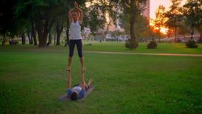 Pousse de plan rapproché de jeune mâle et de formation femelle pose de pied-à-main d'inverse d'acroyoga une basse en parc dehors banque de vidéos