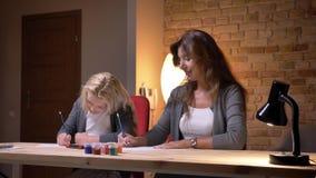 Pousse de plan rapproché de jeune mère et sa petite jolie de fille dessinant ensemble et partageant leurs images Maman de soin banque de vidéos