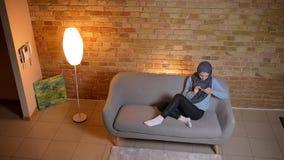 Pousse de plan rapproché de jeune transmission de messages femelle musulmane attrayante au téléphone étant détendu sur le divan à banque de vidéos