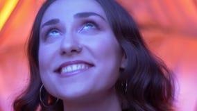 Pousse de plan rapproché de jeune visage femelle caucasien attrayant avec de jolis yeux regardant la caméra avec le fond rouge au banque de vidéos