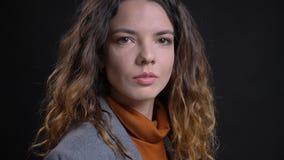 Pousse de plan rapproché de jeune visage femelle caucasien attrayant avec les cheveux bouclés de brune regardant la caméra avec i photos stock