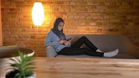 Pousse de plan rapproché de jeune Web surfant femelle musulman attrayant au téléphone tout en se reposant laidback à l'intérieur  banque de vidéos