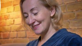 Pousse de plan rapproché de la femelle caucasienne d'eldery soulevant sa tête et regardant la caméra souriant heureusement à la m clips vidéos