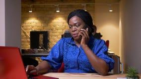 Pousse de plan rapproché de la femme d'affaires adulte d'afro-américain ayant une conversation au téléphone tout en à l'aide de l banque de vidéos