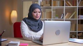 Pousse de plan rapproché de la femme d'affaires réussie musulmane adulte dactylographiant sur l'ordinateur portable et ayant une  clips vidéos