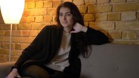 Pousse de plan rapproché de la jeune femelle caucasienne attirante étant détendue et de la TV de observation tandis que schilling photographie stock
